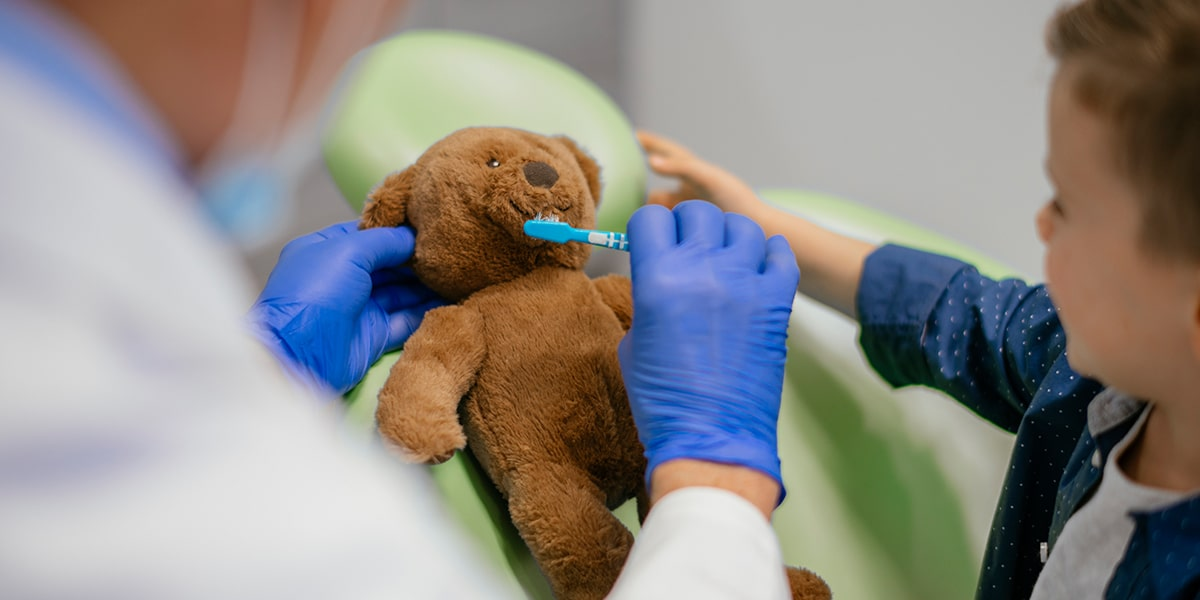 Child Brushing Teddy Bear's Teeth Image
