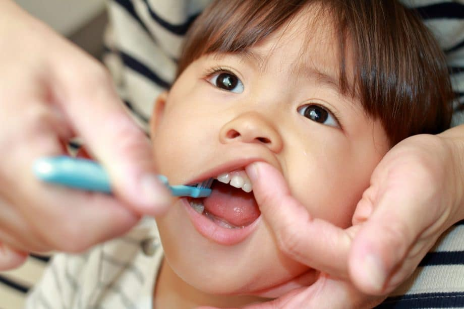 Toddler getting teeth brushed with blue toothbrush by parent