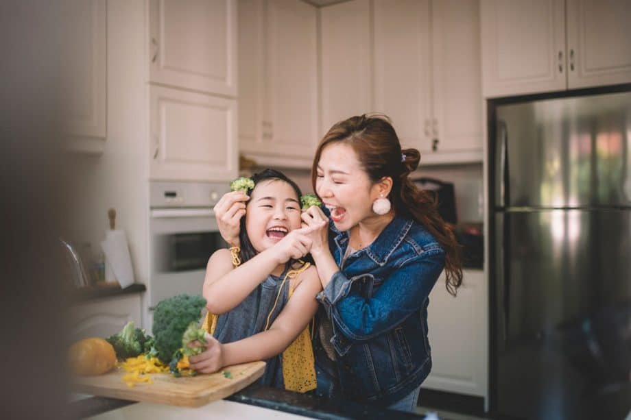 Mother and daughter laughing and preparing food in kitchen